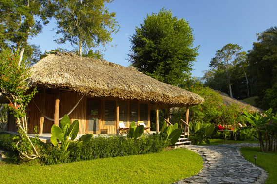 chan chich lodge, belize, thatched roof cabanas in the heart   of the Mayan empire in Belize and the tropical jungle 